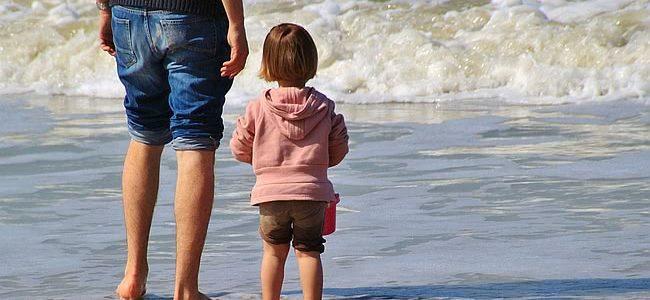 dziecko na plaży z rodzicem